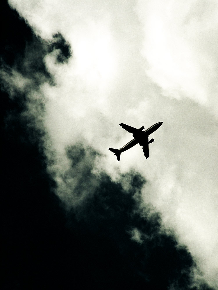 Plane flying overhead, silhouetted by clouds.